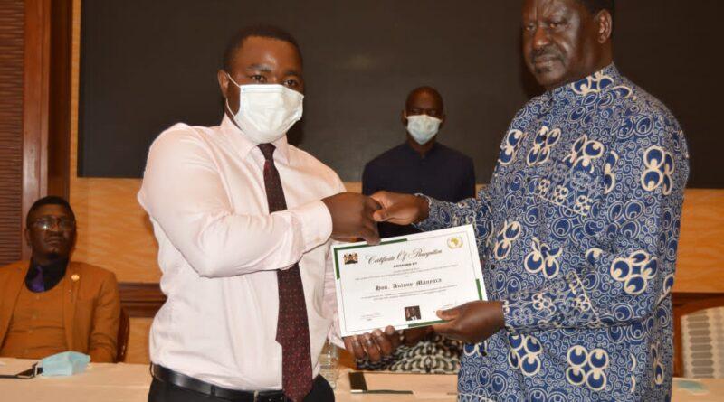 Raila Odinga handing over a certificate
